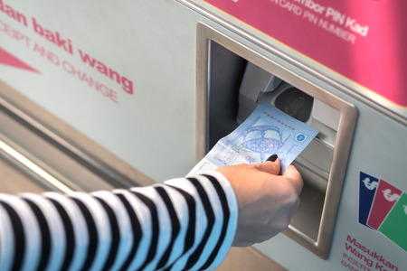 Crop image of hand insert cash for buy train ticket Фото со стока