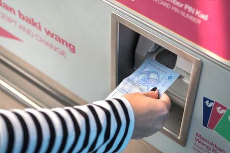 Crop image of hand insert cash for buy train ticket Imagens