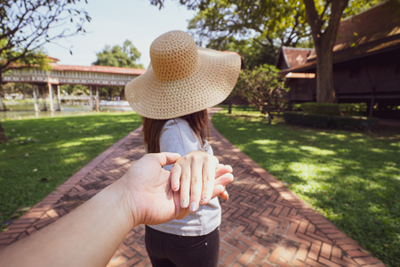 Couple and travel concept. Young woman holding man hand while leading him on public park. Couple in love.