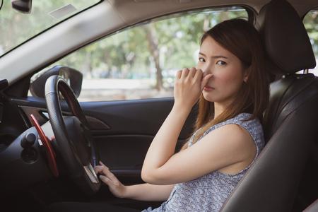 Junge Frau, die ihre Nase wegen des schlechten Geruchs im Auto hält Standard-Bild