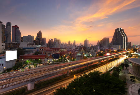 Bangkok cityscape at sunset. Highway and modern office buildings in Bangkok city downtown with sunset sky and clouds at Bangkok, Thailand. Day to night processing. Imagens