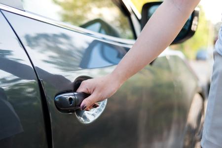 Close up woman hand opening car door. Imagens