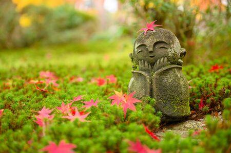 Red Maple leaf on head of Jizo sculpture doll (little Japanese Buddhist monk doll rock) in Japanese Garden