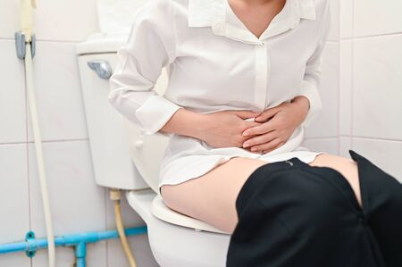 Cropped Woman sitting on toilet bowl and suffering from diarrhea, constipation and cystitis at toilet. Treatment stomach pain and health care
