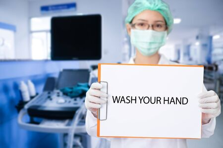 Young asian doctor holding message paper while COVID-19 or coronavirus epidemic situation as wash your hand
