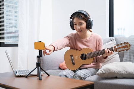 Asian woman blogger recording and live steam playing guitar on social media. Concept of guitarist online lesson while stay at home