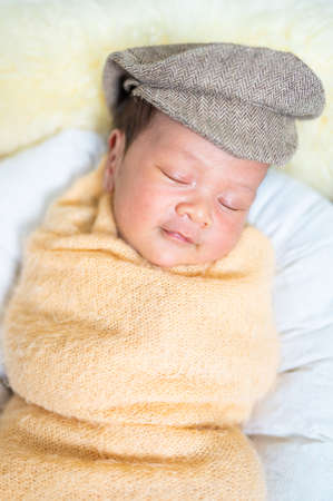 Newborn baby in costume sleeping in baby case Imagens