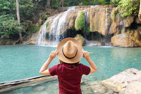 Rear view of young woman traveling in Erawan waterfall in Kanchanaburi Thailand