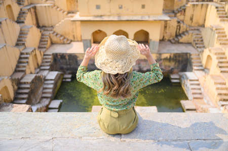 Portrait of young woman traveling in India step-well at Jaipur in Rajasthan state, India