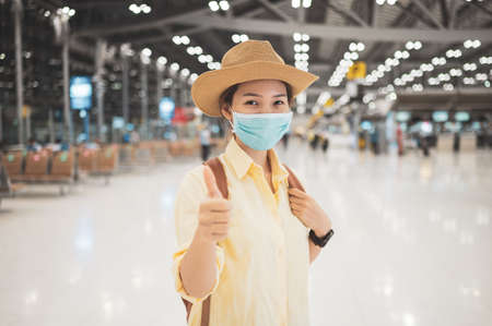 Asian woman backpacker wearing protective face mask giving thumbs up in an international airport. Concept of new normal, safety travel, social distancing and travel bubble