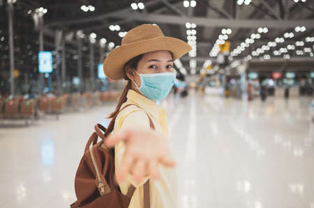 Asian woman backpacker wearing protective face mask raise up hand to holding hand with couple in an international airport. Concept of new normal, safety travel, social distancing and travel bubble