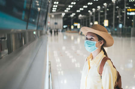 Asian woman wearing protective mask looking at time table screen departure schedule in an airport terminal. Concept of safety travel, coronavirus pandemic and new normal
