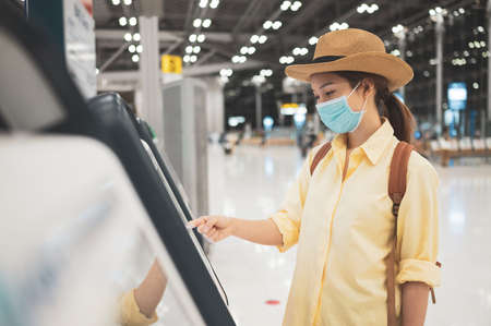 Asian woman wearing face mask  self checking-in printing a boarding pass at the airport while coronavirus pandemic concept of Safety travel under COVID-19 speading
