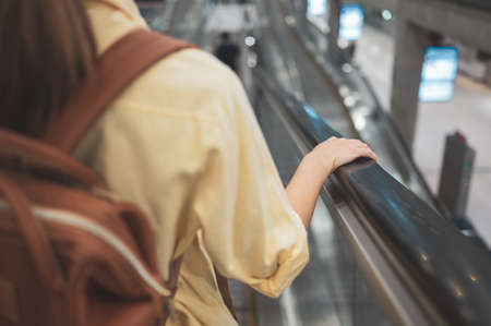 Woman gripping escalator hand rail for safety in public transport terminal