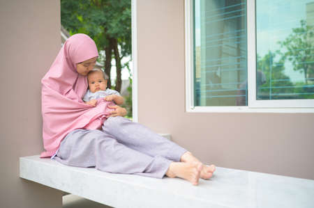 Portrait of muslim woman with newborn baby in her arm Imagens