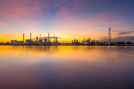 oil refinery plant chemical factory and power plant with many storage tanks and pipelines beside river at sunrise