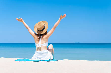 Rear view of  woman wearing sun hat and white bikini spends vacation at the beach on a white sand. summer beach concept