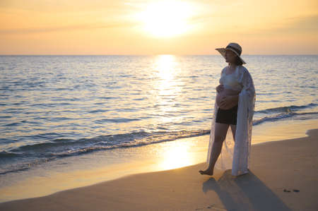 Young Asian pregnant woman relaxing walking on the beach at sunset