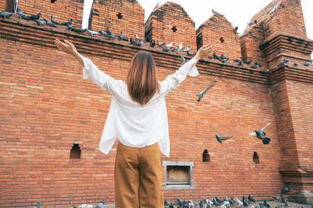 Asian woman traveling at the city wall tha pae gate landmark in Chiang Mai Thailand
