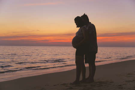 Young family and pregnant wife spend holiday on the beach at sunset Imagens