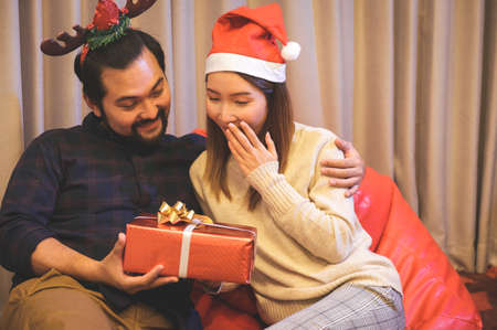 Young Asian couple enjoying to presents Christmas gift at home