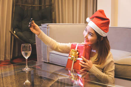 Asian woman celebrating Christmas with boyfriend through a video call online. Coronavirus celebration maintaining the distance Imagens