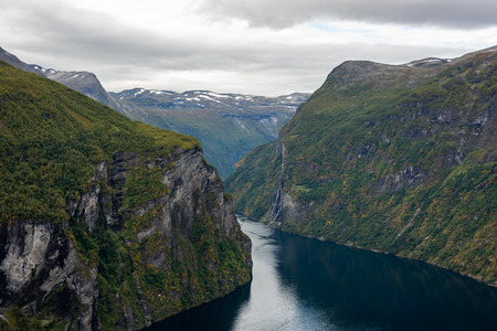 Rainy and cloudy summer day at Geiranger fjord. Showing the waterfall seven sisters and steep cliffs. Banco de Imagens