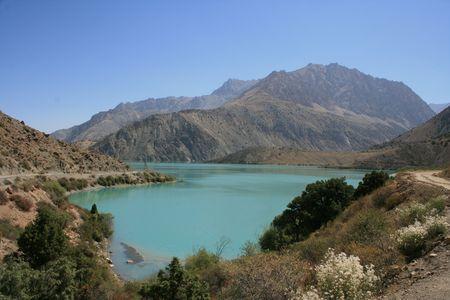 named: Mountain lake named Iskanderkul with trees at the lakeside, Tajikistan Stock Photo