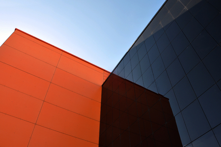 penetracion: Black and orange modern buildings reflect each other. View from below. Foto de archivo