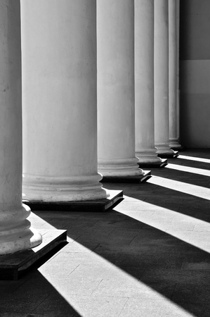 classic contrast: White classical columns with contrasting shadows in perspective. Stock Photo