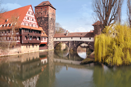 bayern old town: Nuremberg, Bayern, Germany - April 12, 2015. Old buildings, arch bridge and tree reflection in water. Nuremberg, Bayern, Germany on April 12, 2015. Editorial