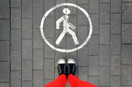 pantalones abajo: Piernas en los pantalones rojos y zapatillas de deporte en el pavimento gris y la señal de tráfico para el tráfico peatonal. Mira abajo.