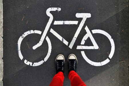 pantalones abajo: Legs in the red pants and sneakers on the gray asphalt, on a background sign of cycle track. Look down.