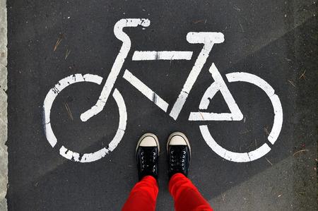 pantalones abajo: Piernas en los pantalones rojos y zapatillas de deporte en el asfalto gris, sobre un fondo de la muestra de la pista para bicicletas. Mira abajo.