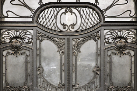 The entrance door to the Art Nouveau style. Elegant metal forged patterns and glass filling. Wroclaw, Poland