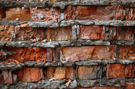 The texture of a ruined wall of red clay bricks and cement mortar. Stock Photo
