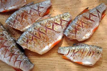 peppered: The process of preparation of river fish on a rustic kitchen. Peppered, salted and incised chub and roach on the wooden surface.