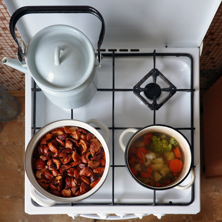 soup kettle: White stove with a pot of stewed fruit, vegetable soup and kettle. View from above. Stock Photo