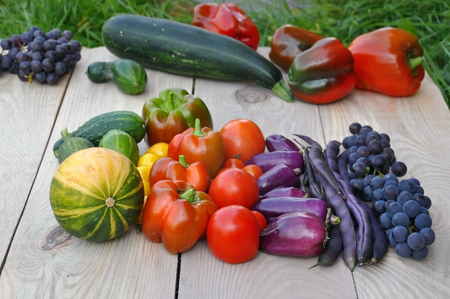 Zucchini, peppers, tomatoes, grapes and beans on a wooden surface close up in perspective.