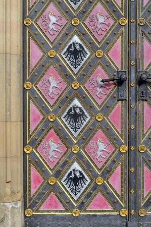 Detail of an old door with a pattern of pink and black rhombus with pictures of eagle and lion. Church in Visegrad, Prague, Czech Republic.