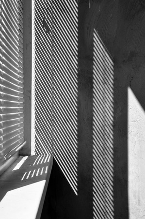 Geometric black and white composition. The plane of the plaster wall with a structural graphic shadow falling from the blinds. Vertical view.
