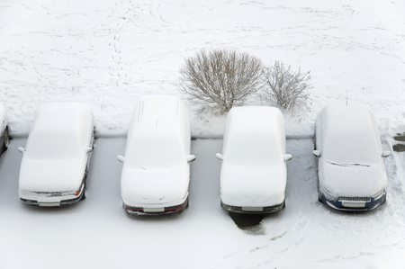 inconvenience: Ground parking cars after snowfall, view from above. Automobiles covered with snow.