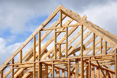 The process of construction of a frame private house with a pitched roof. Wooden frame on the blue sky background.