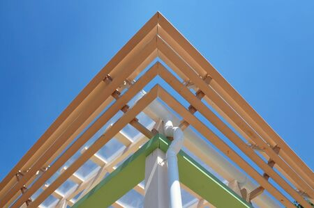 Modern roof construction. Multilevel cornice of the roof of a wooden frame with a drain pipe. Symmetrical view, look up. Stock Photo