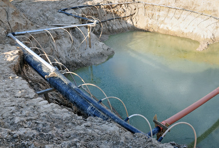 The process of lowering the groundwater level. Industrial sand quarry and a metal tube around it with thin tubes directed at the ground. Stock Photo