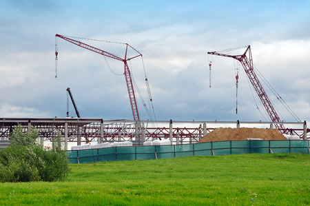 Two cranes and construction in perspective against the blue sky. Green grass in the foreground.