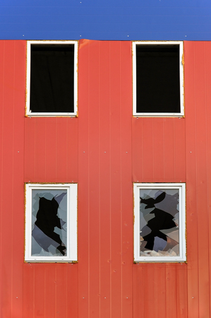 smithereens: Abandoned industrial building. Red wall of sandwich-panels and windows with broken glass