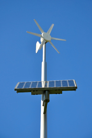 radiacion solar: White support with moving small wind turbine and installed solar panels on a blue sky background.