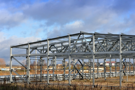 rafter: Metal frame of an industrial building, warehouse in the construction process in perspective. Stock Photo