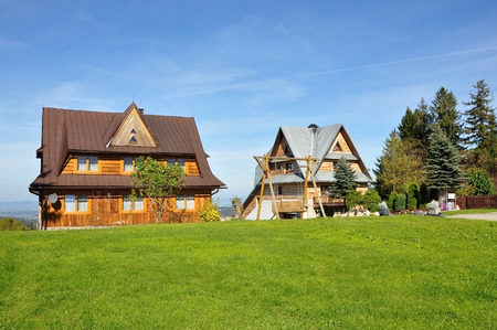 Two private houses with pitched roof in Zakopane style on a background of green grass and blue sky. Stock Photo